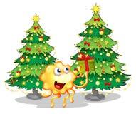 Un monstruo cerca de los dos árboles de navidad verdes Imagen de archivo