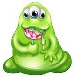 Un monstruo del bebé del greenslime que come una piruleta Imagen de archivo