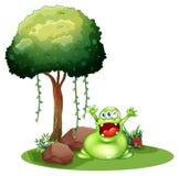 Un monstruo feliz cerca del árbol Foto de archivo libre de regalías
