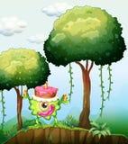 Un monstruo que lleva una torta en el bosque Fotos de archivo libres de regalías
