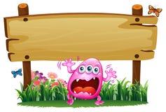 Un monstruo rosado asustado debajo del letrero de madera Foto de archivo