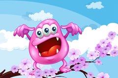 Un monstruo rosado de la gorrita tejida sobre la rama de un árbol Fotos de archivo