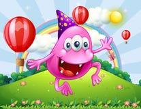 Un monstruo rosado feliz de la gorrita tejida que salta en la cumbre Imagen de archivo libre de regalías