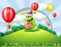 Un monstruo verde feliz que celebra su cumpleaños en la cumbre Imagen de archivo