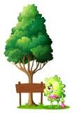 Un monstruo verde que llora al lado del letrero de madera vacío Fotografía de archivo libre de regalías