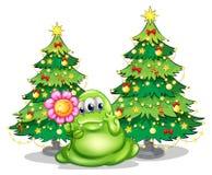 Un monstruo verde que sostiene una flor sonriente Imágenes de archivo libres de regalías