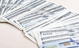 Un montón de billetes de banco de los dólares dispuestos en línea juntos Fotografía de archivo libre de regalías
