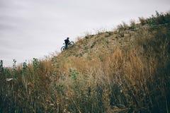 Un montar a caballo del ciclista al top de la colina Imagen de archivo