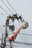 Un monteur de lignes électrique travaillant sur une ligne Image stock