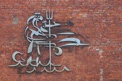 Un monumento a Nettuno su un muro di mattoni Fotografie Stock Libere da Diritti