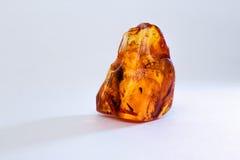 Un morceau d'ambre cru sur une table blanche Photos libres de droits