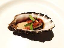 Un morceau d'huître fraîche d'un plat blanc avec de la sauce et l'ail à Yuzu de soja Photographie stock