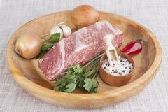 Un morceau de boeuf marbré frais, poivre de piment, persil, oignon, ail, nervures se trouvent sur un plateau en bois Photographie stock