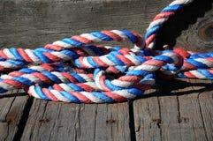 Un morceau de corde rouge, blanche et bleue a lové sur un dock Photo stock
