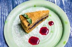 Un morceau de gâteau brun délicieux avec la menthe et baisses de confiture, d'un plat vert, sur un fond bleu de denim photo stock