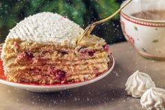 Un morceau de gâteau de canneberge couvert de la crème blanche du plat sur le fond de l'arbre de Noël Photo stock