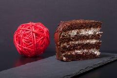 Un morceau de gâteau de chocolat de plat d'ardoise sur le fond noir photo libre de droits