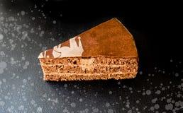 Un morceau de gâteau est isolé sur un fond foncé images stock