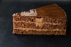 Un morceau de gâteau est isolé sur un fond foncé images libres de droits