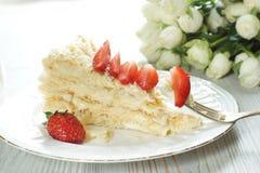 Un morceau de gâteau de napoléon d'un plat a orné avec une fraise mûre rouge, une fourchette avec un morceau coincé de dessert Photo stock