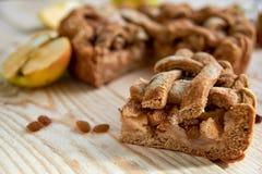 Un morceau de la tarte aux pommes faite maison et les raisins secs bruns se ferment sur le fond en bois clair La tarte aux pommes Photographie stock libre de droits