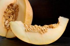 Un morceau de melon jaune doux frais coupé en tranches sur la table noire en bois Morceau de melon organique cru sur la fin foncé Photo stock