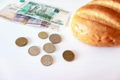Un morceau de pain blanc, de pièces de monnaie et de roubles de papier sur la table Le concept de la pauvreté, manque d'argent po photos libres de droits