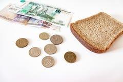 Un morceau de pain noir, de pièces de monnaie et de roubles de papier sur la table Le concept de la pauvreté, manque d'argent pou photographie stock libre de droits