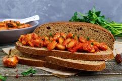 Un morceau de pain de seigle avec des haricots Haricots cuits en sauce tomate avec des herbes et des épices sur la table Images libres de droits