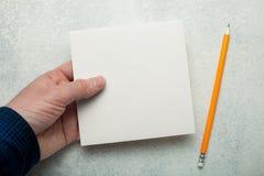 Un morceau de papier carré vide dans la main d'un homme, un crayon jaune à côté de elle Maquette image stock