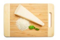 Un morceau de parmesan et de fromage râpé sur le fond de blanc de planche à découper Image stock