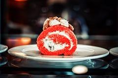 Un morceau de petit pain de gâteau dans la couleur exceptionnellement rouge dans l'intérieur sur les plats blancs images stock