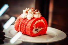 Un morceau de petit pain de gâteau dans la couleur exceptionnellement rouge dans l'intérieur sur les plats blancs image stock