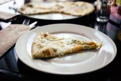 un morceau de pizza chaude fraîche avec du fromage et Basil d'un plat rond blanc dans le restaurant images stock