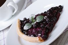 Un morceau de tarte de myrtille avec la menthe d'un plat et d'un café Photos libres de droits