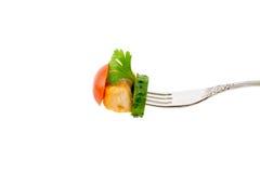 Un morceau de viande frite avec des légumes sur une fourchette sur un fond blanc Photo stock