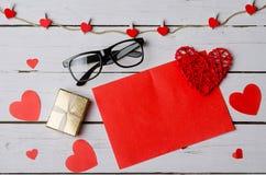 Un morceau rouge de papier et de boîte-cadeau sur un fond en bois blanc Photos stock