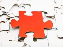 Un morceau rouge sur la pile des puzzles denteux blancs Images stock
