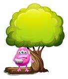 Un mostro rosa danneggiato del beanie che sta sotto l'albero gigante Immagini Stock Libere da Diritti
