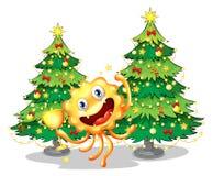 Un mostro vicino agli alberi di Natale che tengono un trofeo Immagini Stock