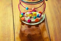 Un mot AMOUR et Coeur-forme de sucrerie de gelée dans un pot en verre courtisent dessus Photos stock