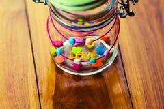 Un mot AMOUR et Coeur-forme de sucrerie de gelée dans un pot en verre sur en bois Images libres de droits