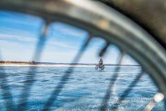 Un motociclista guida attraverso ghiaccio nell'inverno Fotografie Stock
