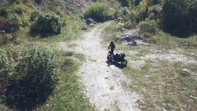 Un motociclista guida la sua bici su una strada non asfaltata video d archivio