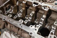 Un motor de cuatro cilindros desmontado y quitado del coche en un banco de trabajo en un taller de la reparación del vehículo aut foto de archivo