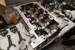 Un motor de cuatro cilindros desmontado y quitado del coche en un banco de trabajo en un taller de la reparación del vehículo Ind foto de archivo