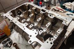 Un motor de cuatro cilindros desmontado y quitado del coche en un banco de trabajo en un taller de la reparación del vehículo fotografía de archivo libre de regalías