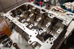 Un motor de cuatro cilindros desmontado y quitado del coche en un banco de trabajo en un taller de la reparaci?n del veh?culo Ser fotografía de archivo