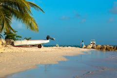 Un motor, palmas, mujer en encorvadura azul en la orilla del océano Playa de Worthing en Barbados imagenes de archivo