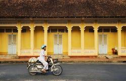 Un motorino di guida della donna sulla strada rurale in Tay Ninh, Vietnam Immagini Stock